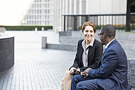 Businesswoman and businessman talking outdoors - WESTF22609
