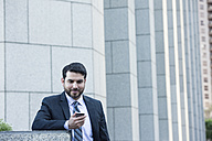 Businessman looking at cell phone - WESTF22612