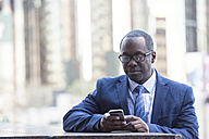 Businessman checking cell phone outdoors - WESTF22618