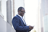 Businessman checking cell phone outdoors - WESTF22630