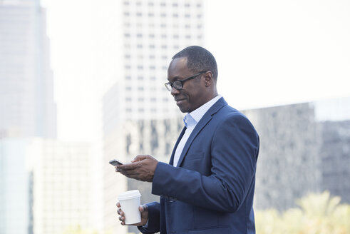 Businessman checking cell phone outdoors - WESTF22633