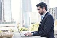 Businessman using laptop outdoors - WESTF22639