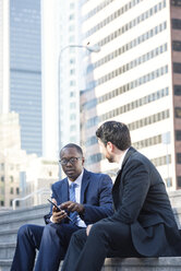 Two businessmen sitting on stairs talking and sharing tablet - WESTF22645