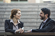 Businesswoman and businessman talking outdoors - WESTF22648