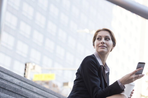 Smiling businesswoman holding cell phone and takeaway coffee - WESTF22651