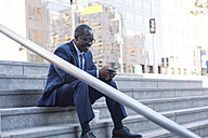 Smiling businessman sitting on stairs checking cell phone - WESTF22654