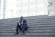 Businessman sitting on stairs with cell phone and takeaway coffee - WESTF22657