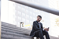Businessman sitting on stairs with cell phone and takeaway coffee - WESTF22663