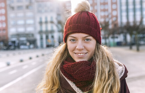Portrait of smiling teenage girl wearing woolly hat and scarf - MGOF02902