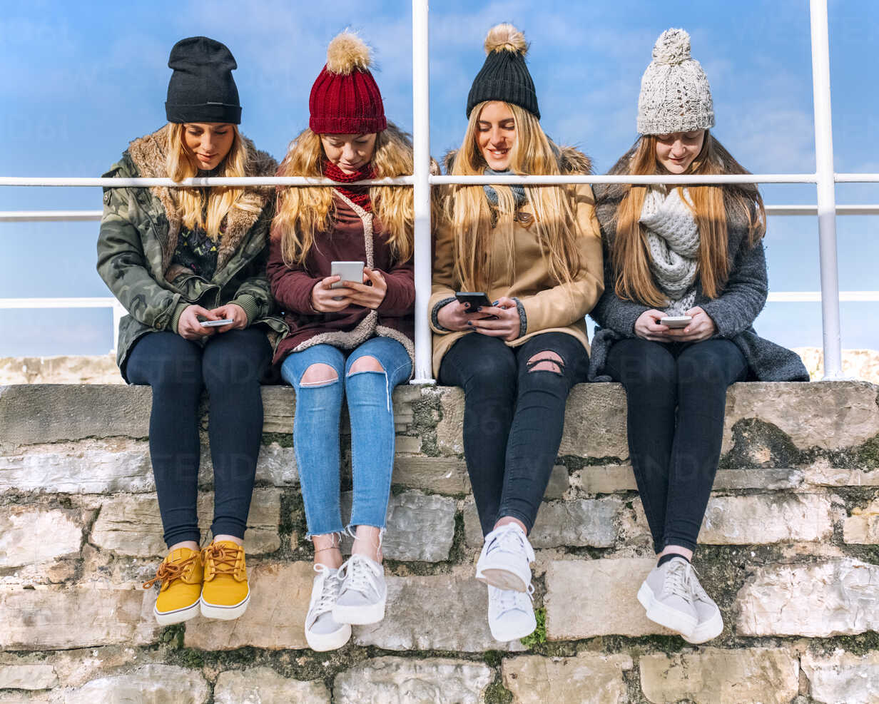Four friends sitting side by side on a wall text messaging - MGOF02905 - Marco Govel/Westend61