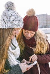 Two teenage girls wearing bobble hats and scarfs looking at smartphone - MGOF02908