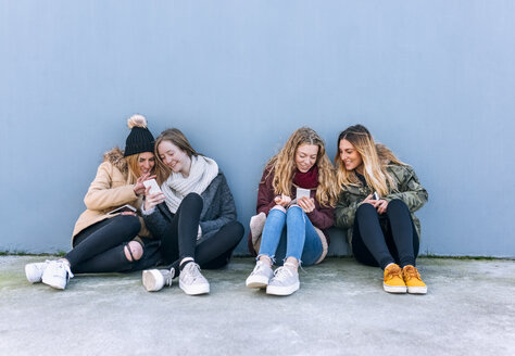 Four friends sitting side by side on the ground looking at cell phones - MGOF02923