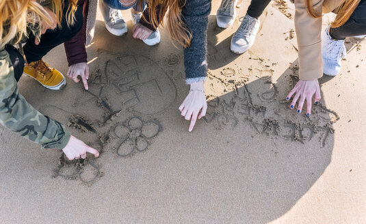Four friends drawing in the wet sand on the beach, partial view - MGOF02926
