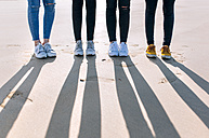 Legs of four friends standing side by side on the beach - MGOF02929