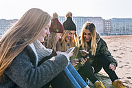 Four friends sitting on the beach text messaging - MGOF02932