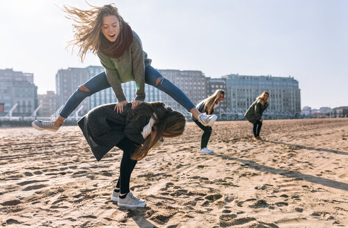Four friends playing leapfrog on the beach - MGOF02935