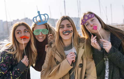 Group picture of four friends with toy moustaches, sunglasses and crowns - MGOF02944