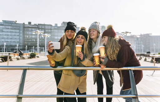 Four friends with coffee to go taking a selfie with smartphone - MGOF02947