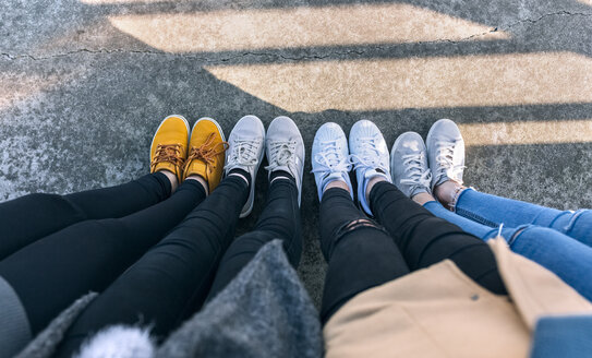 Legs of four friends standing side by side - MGOF02950