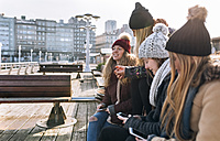 Spain, Gijon, four friends using their cell phones outdoors - MGOF02953