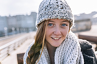 Portrait of smiling teenage girl wearing woolly hat and scarf - MGOF02956