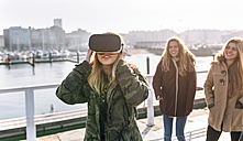 Teenage girl using wearing VR glasses while her friends watching her - MGOF02968
