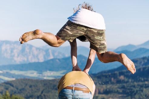 Austria, Mondsee, Mondseeberg, two young men leapfrogging - WVF00836