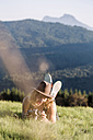 Austria, Mondsee, Mondseeberg, young man with camera lying in meadow - WVF00842