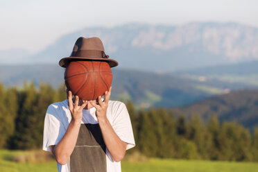 Austria, Mondsee, Mondseeberg, young man covering his face with a basketball - WVF00845