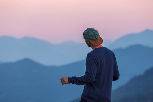 Austria, Mondsee, Mondseeberg, rear view of man wearing a basecap at dusk - WVF00848