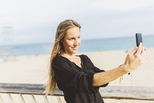 Smiling young woman taking a selfie at the beach - GIOF01820
