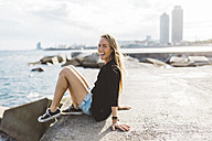 Portrait of happy young woman sitting at the seafront - GIOF01829
