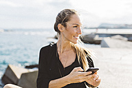 Smiling young woman with cell phone at the seafront  looking around - GIOF01835