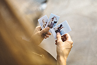 Young woman looking at instant photos of herself - GIOF01844