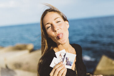 Cheeky young woman showing instant photos of herself at the seafront - GIOF01847