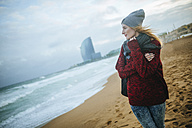 Spain, Barcelona, young woman on the beach in winter - KIJF01184