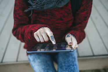 Close-up of tattooed woman's hands using tablet - KIJF01196
