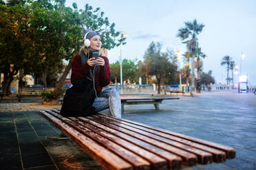 Young woman sitting on a bench listening to music with a smartphone - KIJF01205
