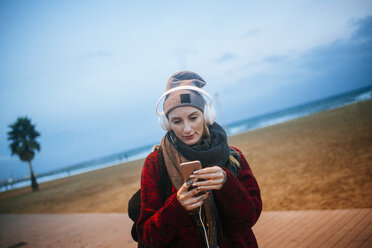 Young woman listening to music on a smartphone on the beach at dusk - KIJF01208