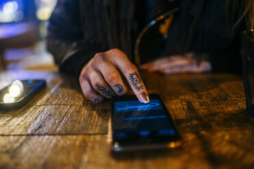 Close-up of hands of tattooed woman signing on a smart phone - KIJF01211