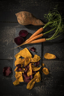 Vegetable chips made of carrots, sweet patatoes and beetroot on dark wood - MAEF12134