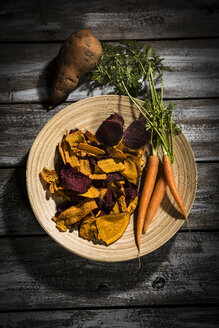Vegetable chips made of carrots, sweet patatoes and beetroot on plate and dark wood - MAEF12137