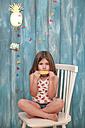 Little girl sitting on chair eating lemon ice lolly - RTBF00651