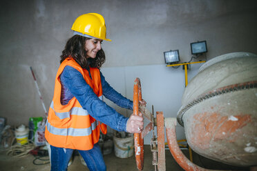 Woman working with a concrete mixer on construction site - KIJF01215