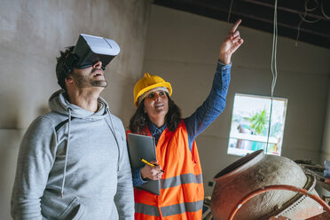 Woman on construction site showing a man with virtual reality glasses the house - KIJF01218