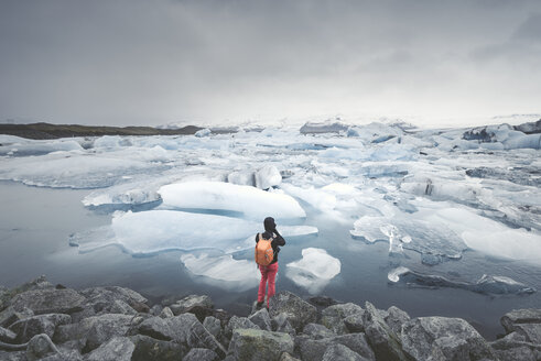 Iceland, view of Joekulsarlon, glacial river lagoon with man standing in the foreground - EPF00322