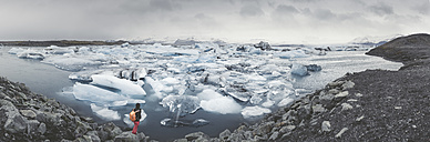 Iceland, panoramic view of Joekulsarlon, glacial river lagoon with man standing in the foreground - EPF00325