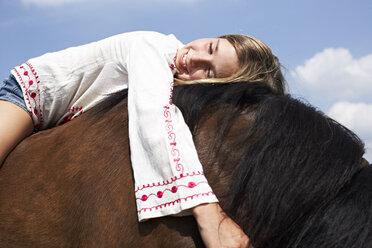 Happy girl lying on horseback - FSF00779