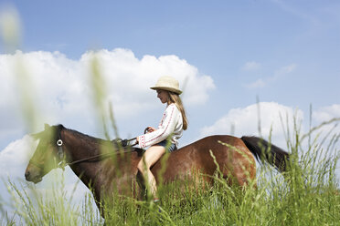 Girl riding horse on meadow - FSF00782