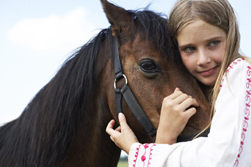 Happy girl hugging horse - FSF00791
